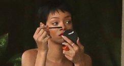 Rihanna wearing stripey dress applying make up