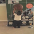 Toddler tries to shoot hoop at picture