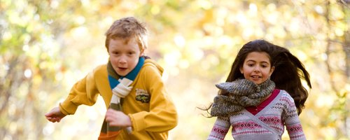 Boy and girl playing in the Autumn leaves